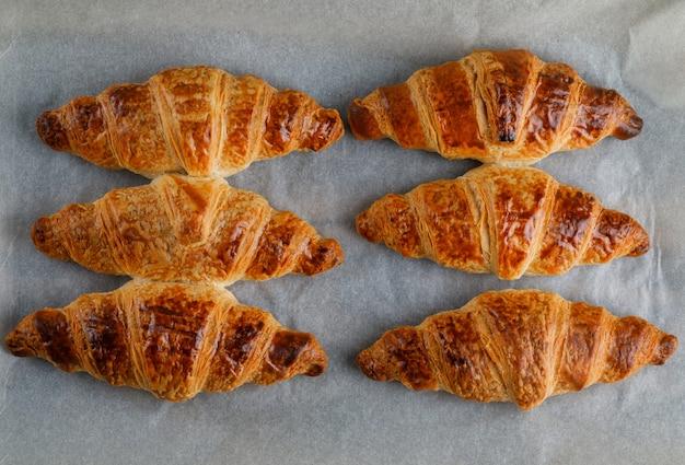 Croissant sobre papel de horno, plano.