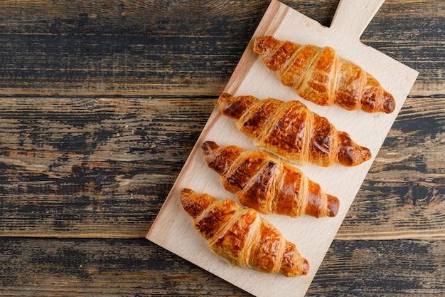 Croissant en tabla de cortar y madera. aplanada