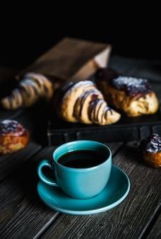 Croissant y taza de café negro sobre lienzo marrón.