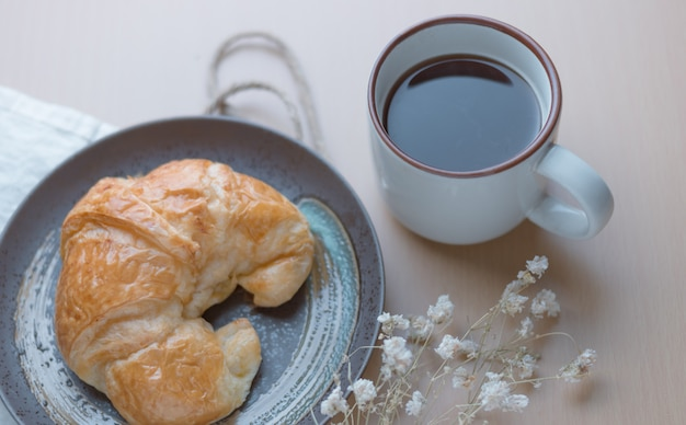 Croissant con una taza de café negro