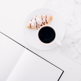Croissant y taza de café en un plato cerca del cuaderno de páginas en blanco