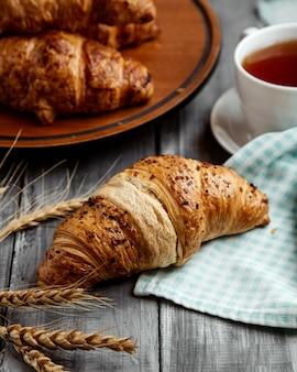 Croissant con taza de mesa de teon