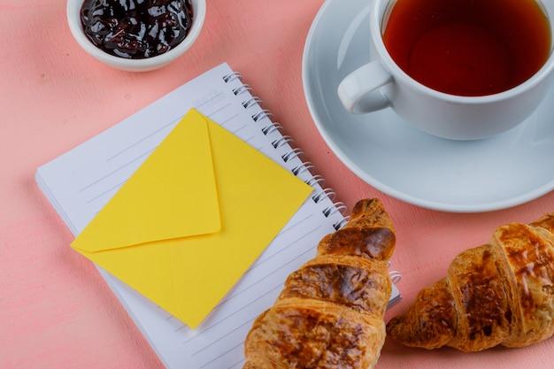 Croissant con té, mermelada, sobre, cuaderno de primer plano sobre una mesa rosa