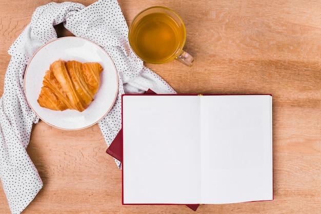 Croissant de vista superior con libro en blanco