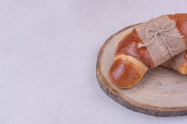 Croissants aislado en una bandeja de madera sobre superficie gris
