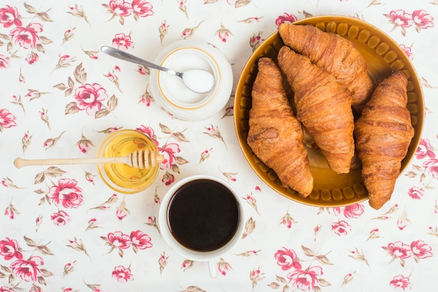 Croissants al horno té; miel y leche en polvo sobre fondo floral.