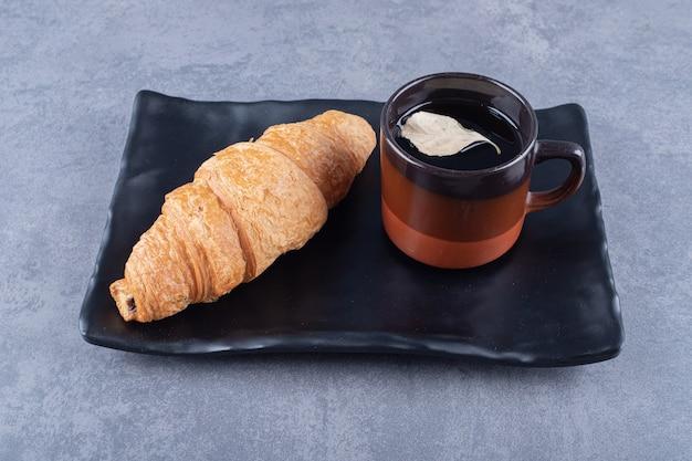 Croissants con café. croissants franceses en plato y taza de espresso.