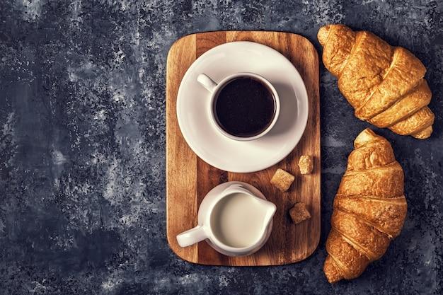 Croissants y café en una mesa oscura