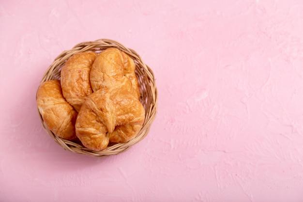 Croissants en la canasta de madera sobre el fondo rosa