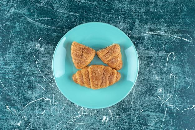 Croissants caseros en un plato, sobre el fondo azul. foto de alta calidad