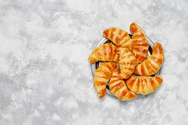 Croissants caseros sabrosos frescos en blanco grisáceo. pastelería francesa