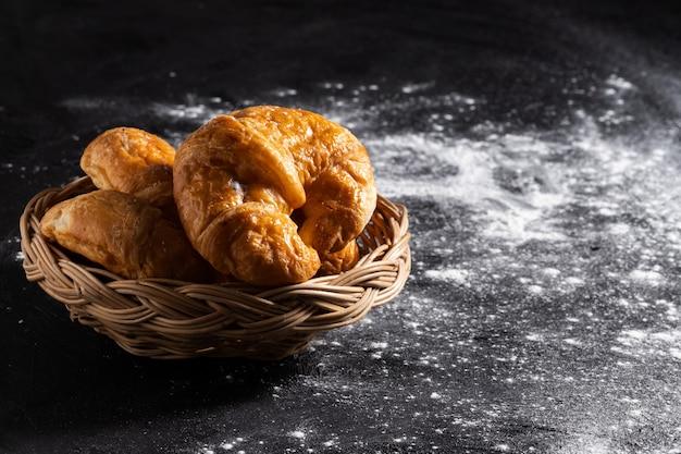 Croissants en una cesta de mimbre colocada en un piso negro