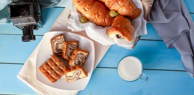 Croissants con crema de chocolate y un vaso de leche sobre la mesa azul. vista superior.