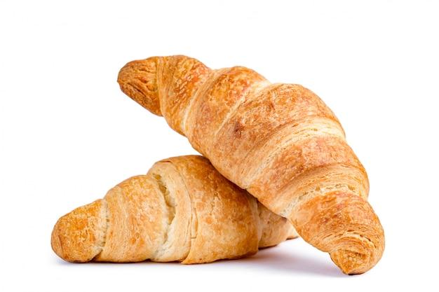 Croissants deliciosos y frescos sobre un fondo blanco.