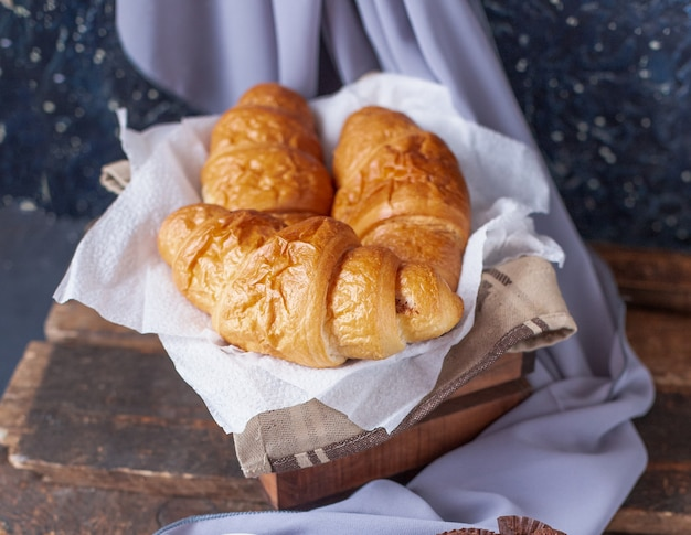 Croissants dentro de una caja de madera sobre un trozo de tejido blanco