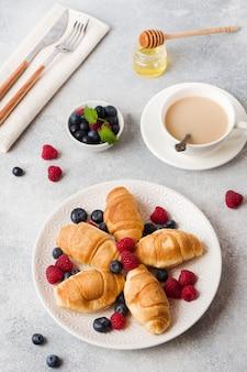Croissants con frambuesas frescas y arándanos sobre una superficie oscura de hormigón