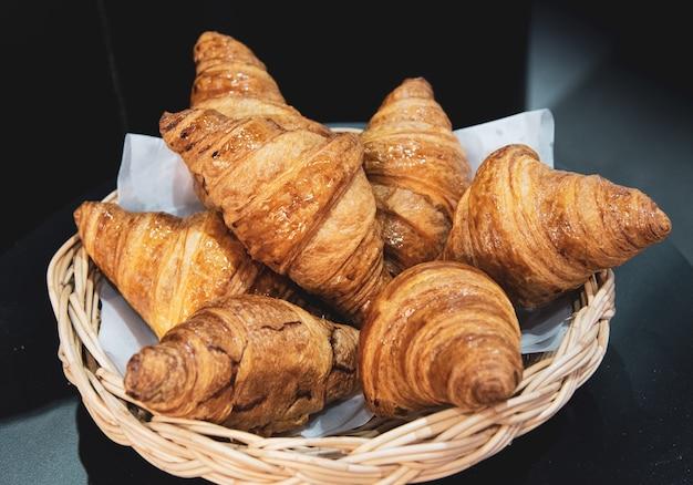 Croissants franceses en cesta de mimbre, fondo de panadería