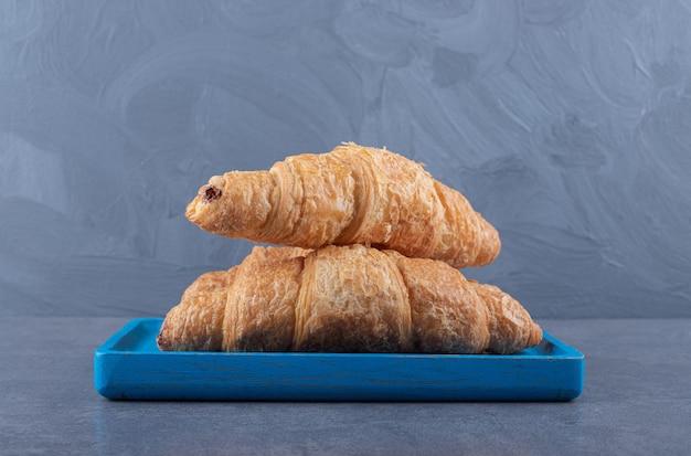 Croissants franceses frescos con corteza dorada. sobre tablero de madera azul.