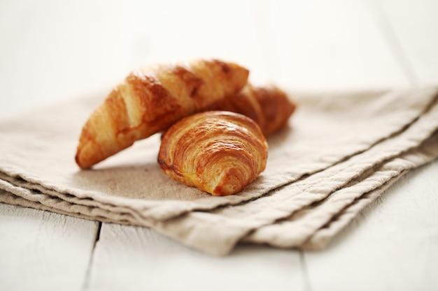 Croissants franceses frescos sobre un mantel
