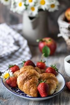 Croissants con fresas rojas frescas con una taza de café en una mesa de madera y ramo de margaritas en una jarra.