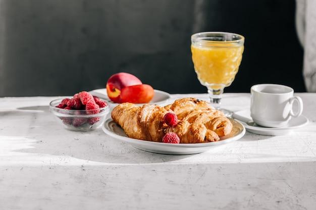 Croissants y frutas con un vaso de jugo.