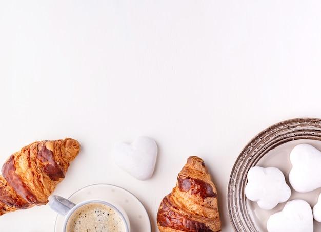Croissants, galletas glaseadas y una taza de café sobre una mesa de madera blanca. mañana bodegón. vista superior con espacio de copia de texto.