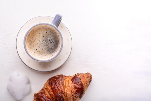 Croissants, galletas glaseadas y una taza de café sobre una mesa de madera blanca.