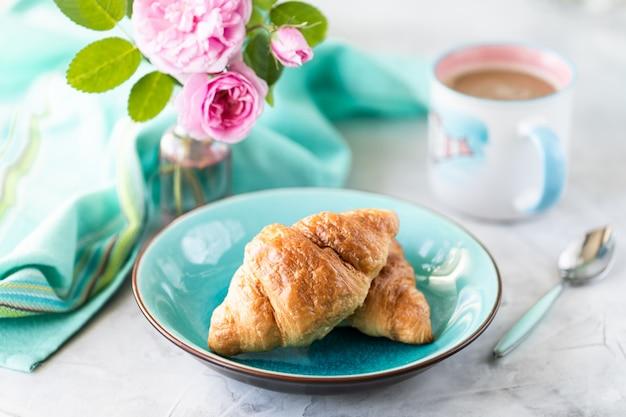 Croissants en un hermoso plato con un ramo de rosas rosadas.