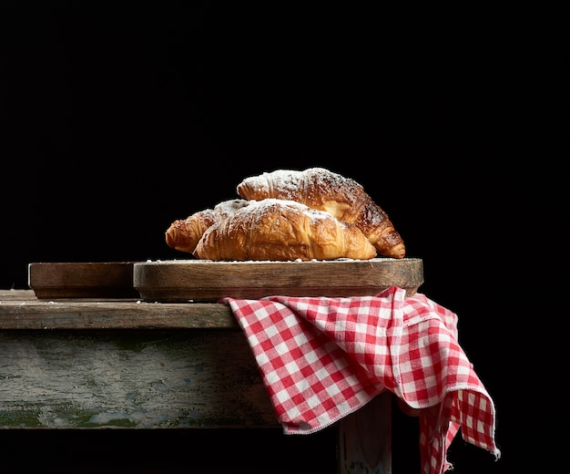 Croissants horneados sobre tablero de cocina marrón, fondo negro,