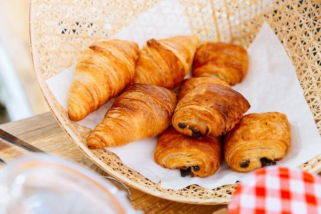 Croissants de mantequilla clásicos recién horneados y croissant de pasas dentro de la cesta de tejido.