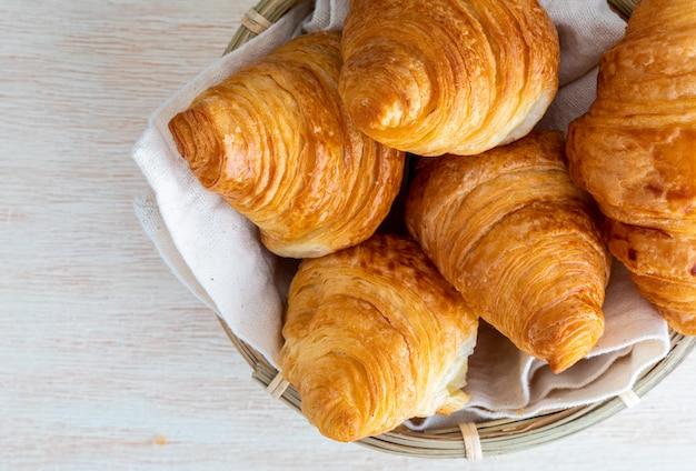 Croissants de mantequilla en una pequeña cesta de mimbre. vista superior