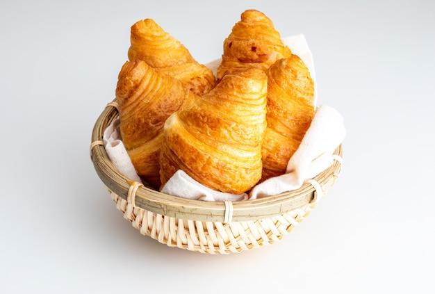Croissants de mantequilla en una pequeña cesta de mimbre.