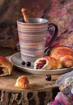 Croissants en un plato con bayas y una taza de café.