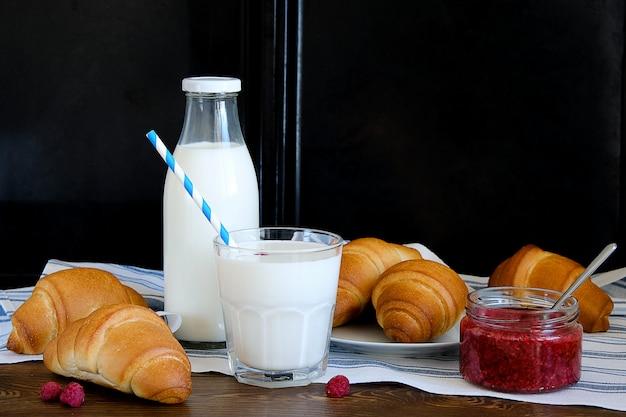 Croissants en un plato, mermelada de frambuesa, leche en una botella y en un vaso sobre una mesa de madera.