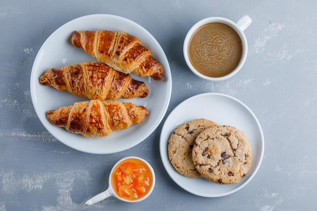 Croissants en un plato con taza de café, galletas, mermelada, vista superior