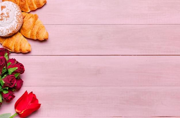 Croissants con ramo de rosas en mesa rosa