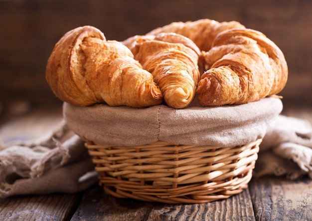Croissants recién hechos en una canasta sobre una mesa de madera