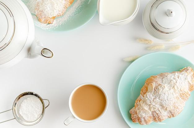 Croissants recién hechos en placas de color turquesa, leche y café sobre fondo blanco.