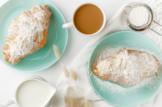 Croissants recién hechos en platos turquesas, leche y café en la mesa blanca