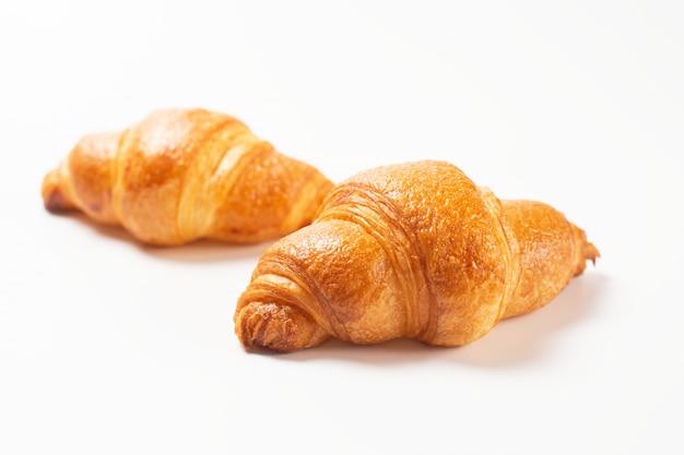 Croissants recién hechos sobre fondo blanco.