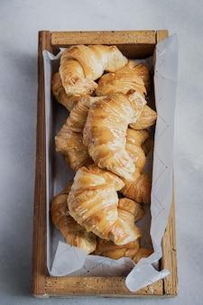 Croissants recién horneados en una caja de madera.