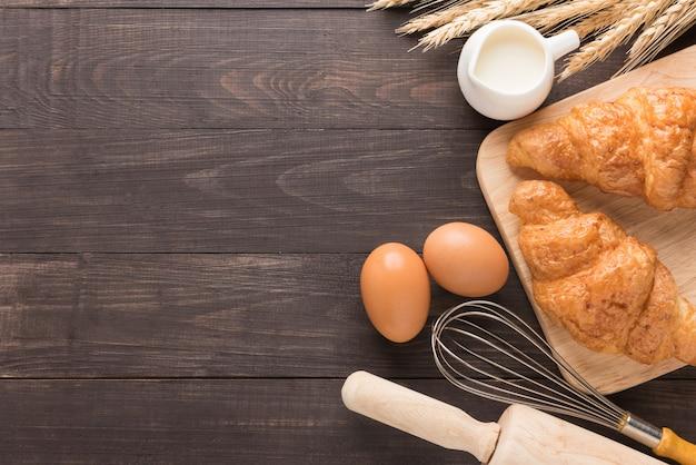Croissants recién horneados, leche y huevos sobre fondo de madera