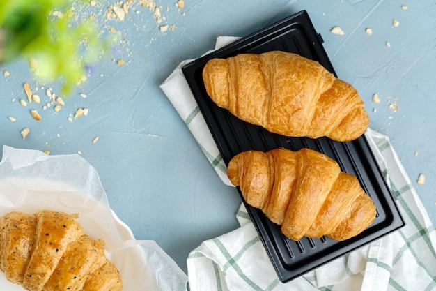 Croissants recién horneados en placa negra.
