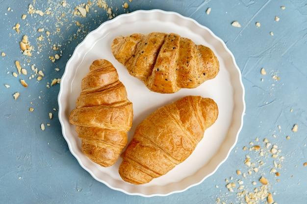 Croissants recién horneados en un plato blanco. francés y americano