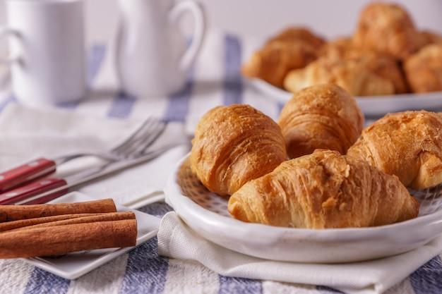 Croissants recién horneados en un plato y canela en rama