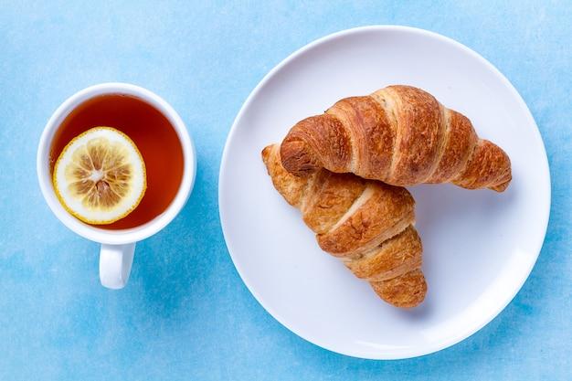 Croissants recién horneados en un plato y una taza de té caliente con limón para el desayuno francés sobre un fondo azul.