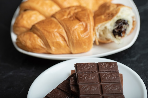 Croissants con relleno de chocolate sobre una superficie oscura.