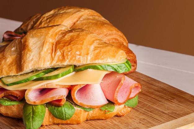 Croissants sándwiches en la tabla de cortar de madera