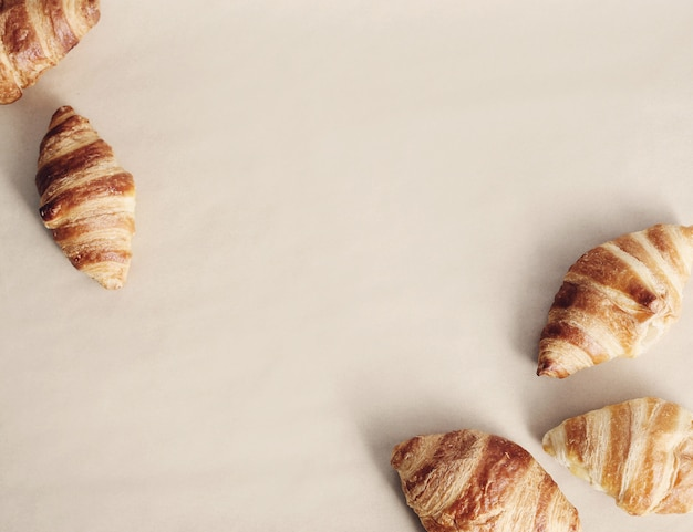 Croissants sobre fondo beige, vista superior de copyspace