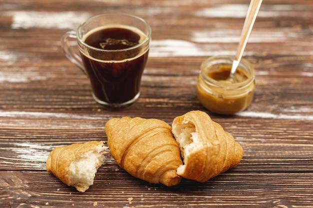 Croissants con taza de café y mantequilla de maní sobre la mesa